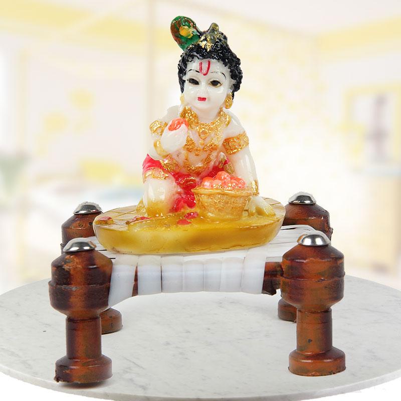 Krishna on the chowki eating Modak