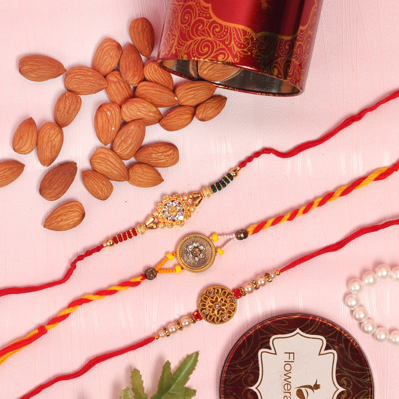 Nut Three Rakhi Set Combo - Set of 3 Designer Rakhi with Complimentary Roli and Chawal and 100gm Almonds in Red Floweraura Container