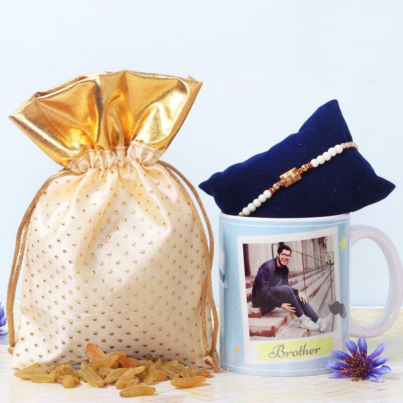 Personalised Rakhi Hamper - One Metal Rakhi with Complimentary Roli and Chawal and Personalised Brother Mug and 100gm Raisins in Cream Potli and One personalised ceramic mug