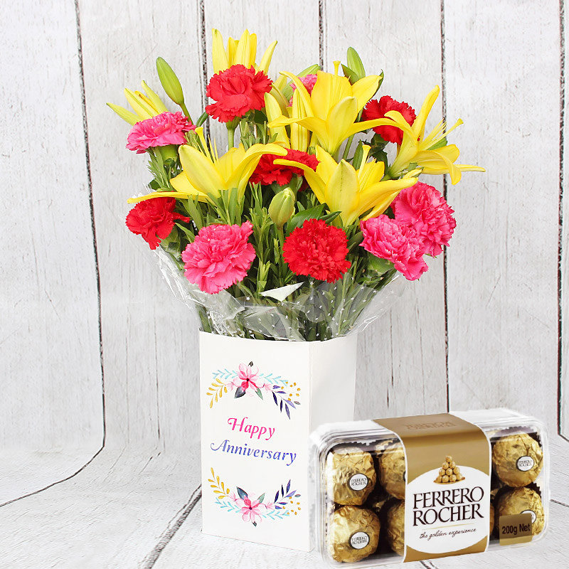 Rocher Anniversary Flowers Combo - Bunch of 10 Red and Pink Carnations with 2 Yellow Lilies and Anniversary Flower Box and Pack of 16 Ferrero Rochers