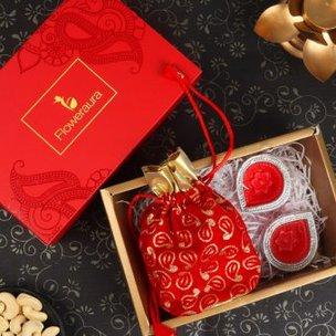 A Floweraura Diwali Gift Box of Cashews in Red Potli with 2 Designer Diyas