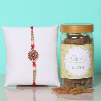 Resin Round Stone Rakhi Combo - One Designer Pearl Rakhi with Complimentary Roli and Chawal and 100gm Raisins in Colorful Floweraura Container